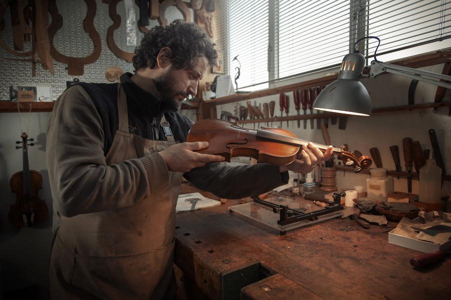 Il liutaio controlla i riflessi della verniciatura
